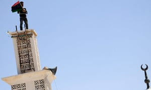 A Libyan rebel fighter waves a Libyan flag from the roof of a mosque in Ajdabiya