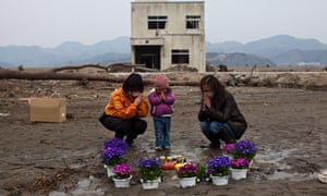 A month after Japan's first earthquake and tsunami a family pray for missing relatives in Ishinomaki