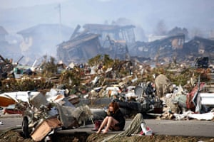 Japan disaster 1 month on: A woman cries while sitting on a road amid rubble in Natori
