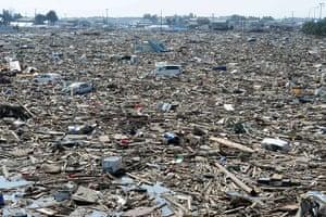 Japan disaster 1 month on: Debris lie strewn across a large area of NAtori