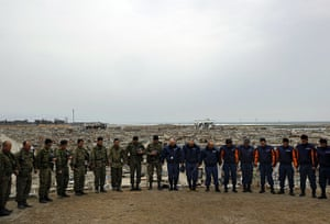 Japan disaster 1 month on: Rescue workers observe a minute silence in  in Natori, Miyagi Prefecture