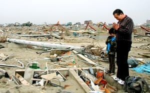 Japan disaster 1 month on:  A man and his grandson offer a prayer at the ruins of a house in Natori