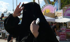 A woman wearing a niqab walks in the Tuileries Garden in Paris