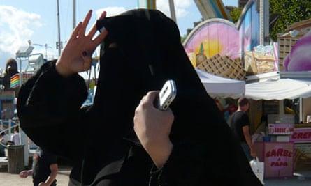 A woman wearing a niqab walks in the Tuileries Garden in Paris