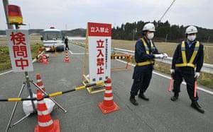Fukushima disaster: 11 April: Police officers man a checkpoint in Minamisoma