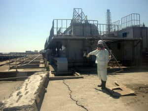 Fukushima disaster: 2 April:A worker wearing a protective suit points at a cracked concrete pit