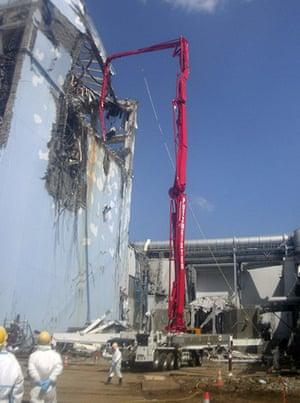 Fukushima disaster: 12 April: Workers pump contaminated water from Unit 4