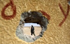 Ajdabiya, Libya : A rebel soldier is seen through a hole in a concrete wall, Ajdabiya