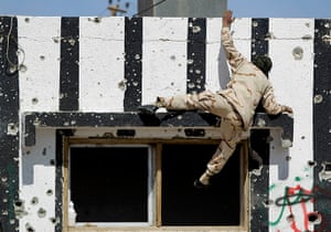 Ajdabiya, Libya : A rebel fighter climbs on top of a building, Ajdabiya