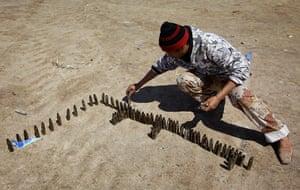 "Ajdabiya, Libya : A rebel makes the Arabic word for ""Libya"" using bullet casings, Ajdabiya"