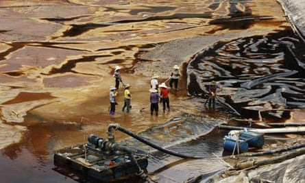 Workers drain away polluted water near the Zijin copper mine