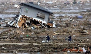 Junior high school students return home through the rubble in Yamamoto, Miyagi, Japan