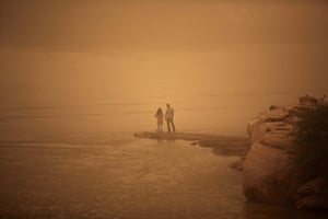 24 hours in pictures: An Iranian couple stand on the shore of the Arvandrud river