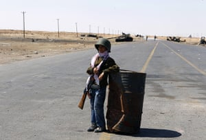 24 hours in pictures: A ten-year-old boy stands guard at a rebel checkpoint  in Ajdabiyah