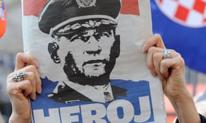 A woman holds a newspaper in Zagreb's main square with a portrait of Croatian general Ante Gotovina