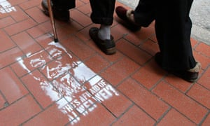 People in Hong Kong walk past street stencils of detained Chinese artist and activist Ai Weiwei