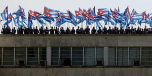 Bay of Pigs anniversary: People wave Cuban flags on a roof during a military parade