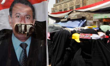 A woman stands near a poster of Yemeni president Ali Abdullah Saleh
