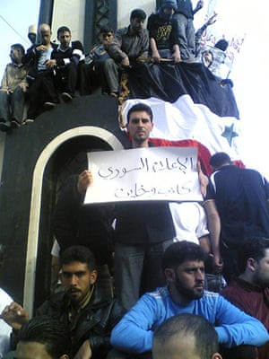 "Syria protests: The placard reads: ""Syrian media liar and a traitor"""