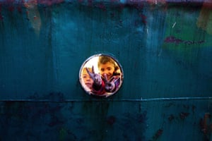 """Misrata, Libya : Libyan girls flash the """"V"""" sign from the porthole of a small ship"""