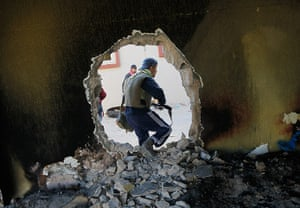 Misrata, Libya : A rebel fighter moves through a hole punched in a wall near the front line