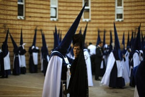 Holy Week in Malaga: Penitents and a woman wearing a traditional mantilla