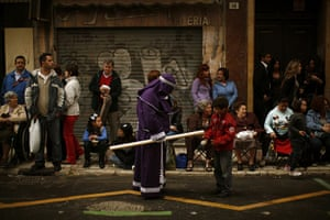 Holy Week in Malaga: A penitent gives wax of a candle to a child
