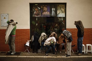 Holy Week in Malaga: People cover up from the rain with their coats