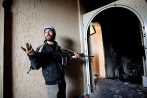 Misrata: In pictures: A Libyan rebel gestures as he enters a building