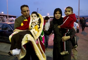 Misrata: In pictures: A family with a wounded child walk towards a ferry