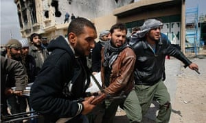 Rebel fighters carry a wounded comrade in Misrata, Libya