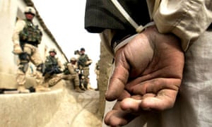 American soldiers watch over a detained man in Afghanistan