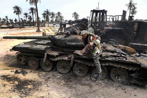 Misrata Libya: A Libyan rebel fighter climbs off of a destroyed tank in Misrata