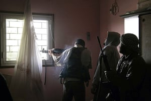 Misrata Libya: A Libyan rebel fighter fires from a window as comrades look on