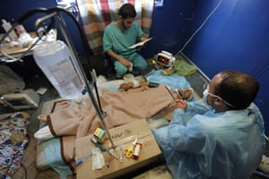 Misrata Libya: A man tends his critically wounded brother who was hit by a mortar blast