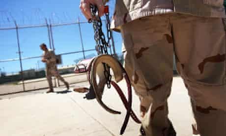 A guard holding leg shackles at Guantánamo Bay