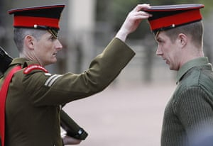 Royal Wedding rehearsal: An officer from the Grenadier Guards adjusts a soldier's cap