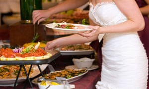 A bride getting food from a buffet at a wedding