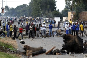 Africa Unrest: Township residents stand near barricades during protests in South Africa