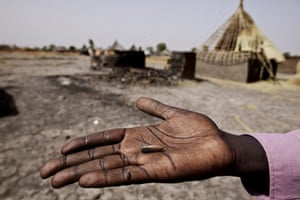 Africa Unrest: A survivor displays a bullet in front of burnt houses in Sudan