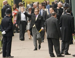 Wedding guests: Sir Elton John waves as he arrives at Westminster Abbey