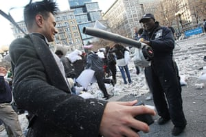 Pillow fight day: New York, USA: A worker uses a leaf blower on a man covered in feathers