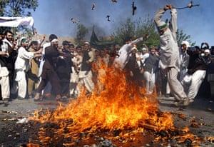Afghanistan protests: An Afghan protestor beats a burning effigy of President Obama in Jalalabad