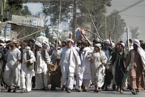 Afghanistan protests: Afghan protesters walk with sticks in Kandahar