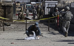 Afghanistan protests: An Afghan policeman collects body parts after an attack at Camp Phoenix