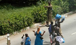 Civilians pass pro-Gbagbo soldier in Abidjan