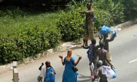 Civilians pass pro-Gbagbo soldier in Abidjan