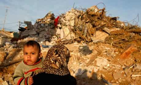 A Palestinian woman carries her child past a demolished house in the Gaza Strip