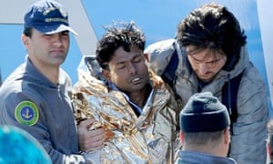 A survivor from the capsized boat is wrapped in foil and taken to get medical treatment in Lampedusa