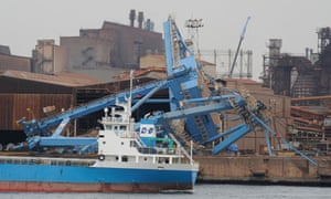A ship goes past a loading crane which collapsed during the March 11 earthquake in Kashima, Japan